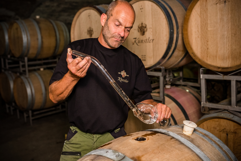 Cellarmaster Rolf Schregel draws a sample from a barrique cask
